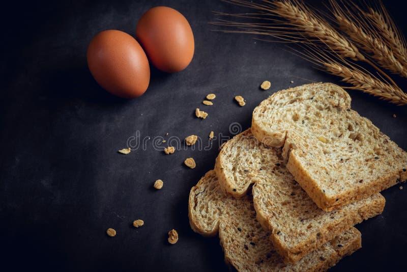 Geheel korrelbrood en ei op donkere achtergrond stock foto's