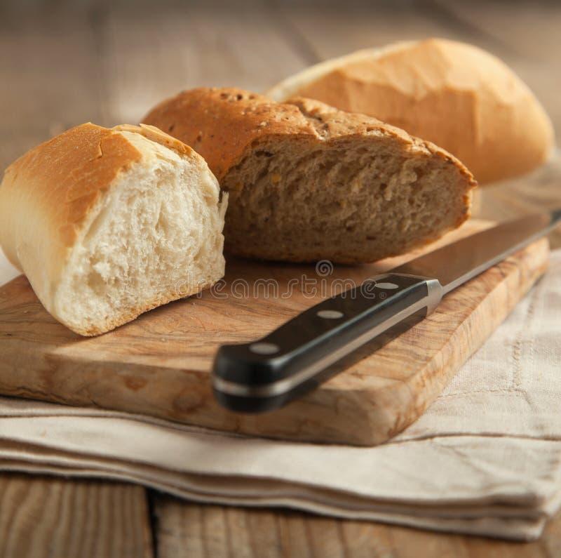 Geheel korrelbrood en wit brood op houten hakbord. royalty-vrije stock foto's