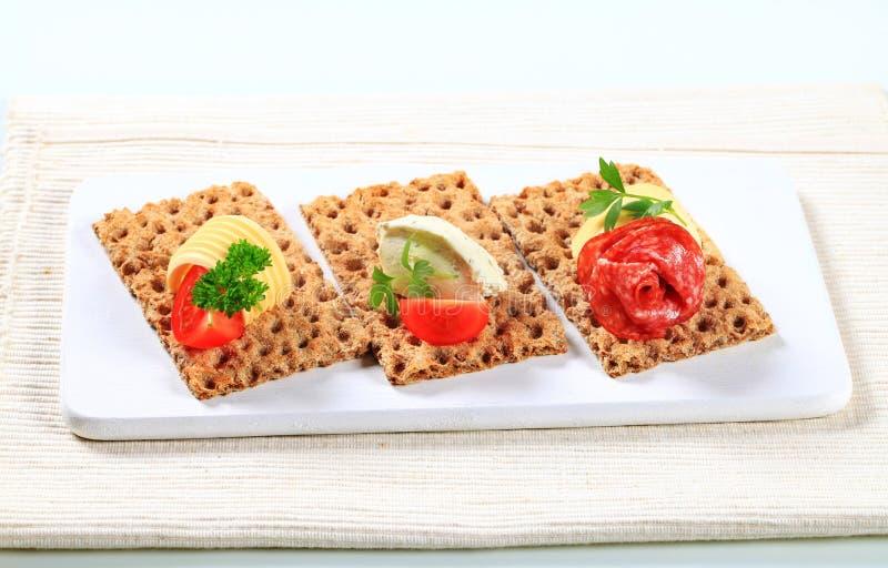 Geheel korrelknäckebrood met diverse bovenste laagjes stock foto