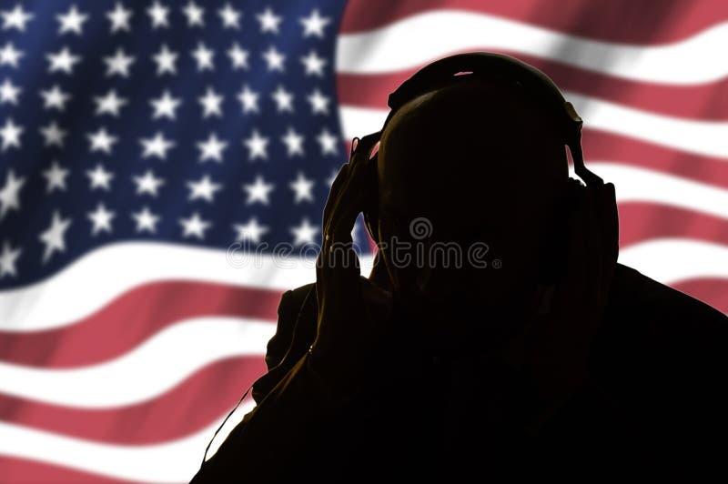 Geheimagent in hoofdtelefoons op de achtergrond van de Amerikaanse vlag royalty-vrije stock fotografie
