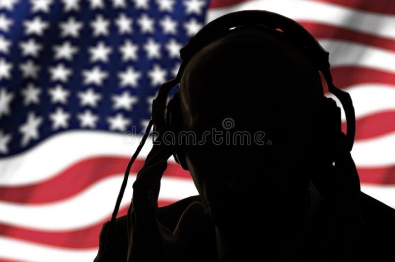 Geheimagent in hoofdtelefoons op de achtergrond van de Amerikaanse vlag royalty-vrije stock foto's