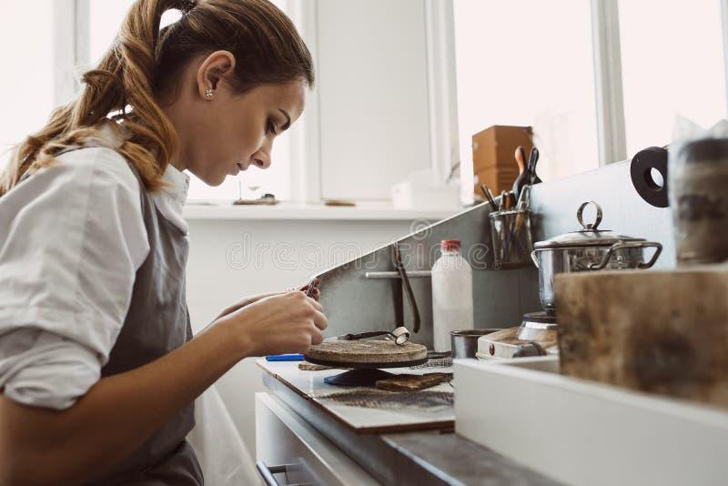 Geheime technologie Zijaanzicht van jonge vrouwelijke juwelier die aan een nieuwe zilveren ring bij haar werkbank werken Juwelen  royalty-vrije stock fotografie