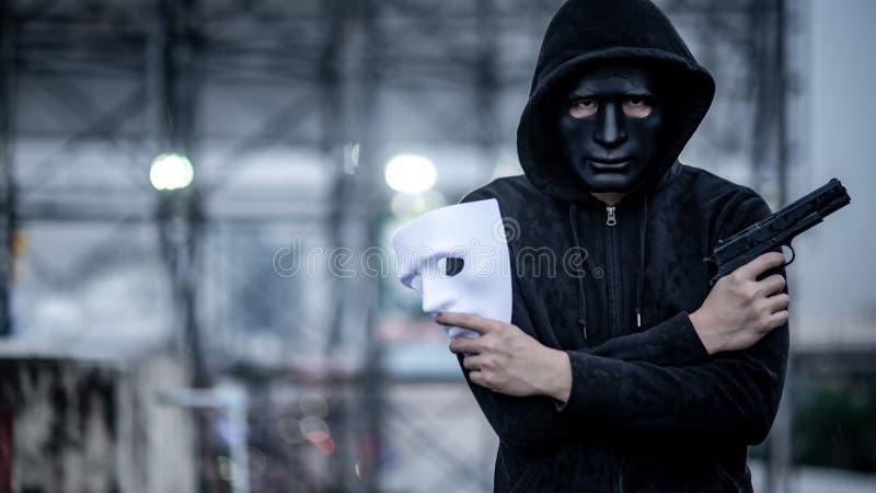 Geheimnis Hoodiemann, der weiße Maske und Gewehr hält lizenzfreie stockbilder