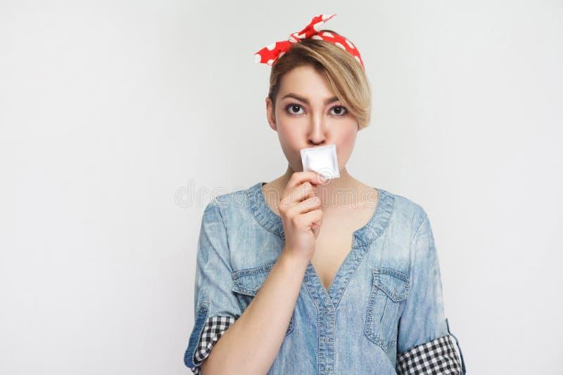 geheimnis Portr?t des attraktiven jungen M?dchens im zuf?lligen Denimhemd mit Make-up, rote Stirnbandstellung, Mund mit Kondom be stockfotos