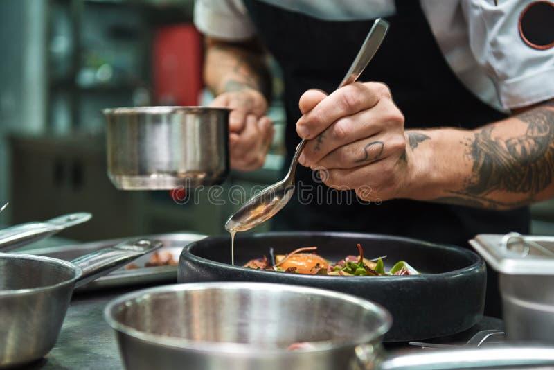 Geheimrezept Nahes hohes Foto von Chefhänden mit einigen Tätowierungen, die eine Soße italienischen Teigwaren Carbonara hinzufüge lizenzfreies stockbild