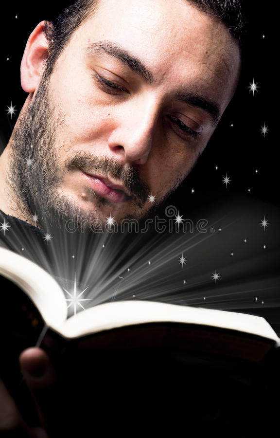 Geheimzinnig boek dat verlicht terwijl de jongen leest stock foto