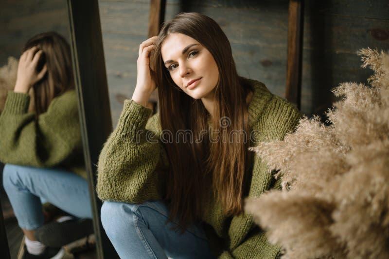 Geheimzinnig glimlachend jong meisje in donkergroene gebreide comfortabele sweater met de schoven van hooisamenstelling en spiege stock fotografie