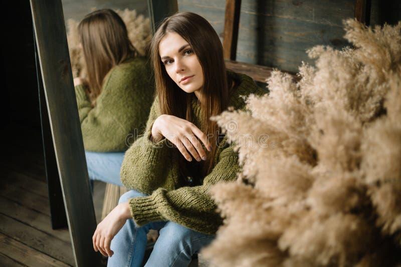 Geheimzinnig glimlachend jong meisje in donkergroene gebreide comfortabele sweaterzitting op de vloer Studio conceptuele foto stock fotografie