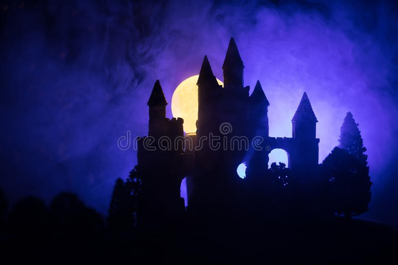 Geheimzinnig middeleeuws kasteel in een nevelige volle maan Verlaten gotisch stijl oud kasteel bij nacht stock fotografie
