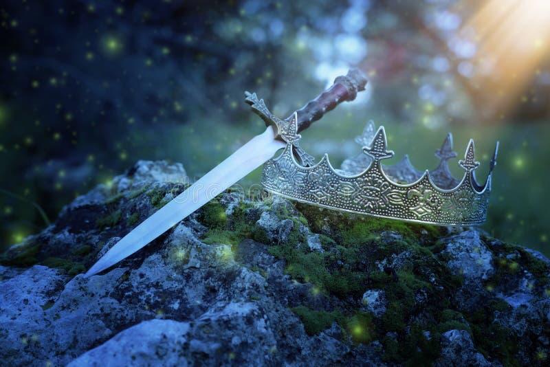 geheimzinnige en magische foto van zilveren koningskroon en zwaard over de steen in het hout van Engeland of gebiedslandschap met stock afbeelding