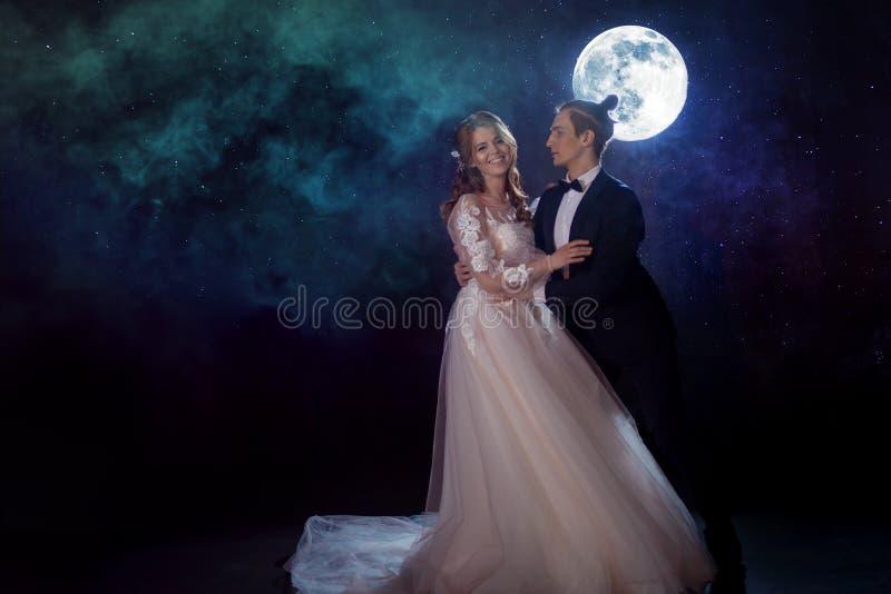 Geheimzinnige en romantische vergadering, de bruid en de bruidegom onder de maan Omhelzingen samen Gemengde media stock fotografie