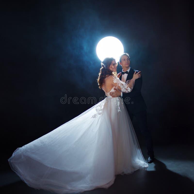 Geheimzinnige en romantische vergadering, de bruid en de bruidegom onder de maan Omhelzingen samen stock foto's