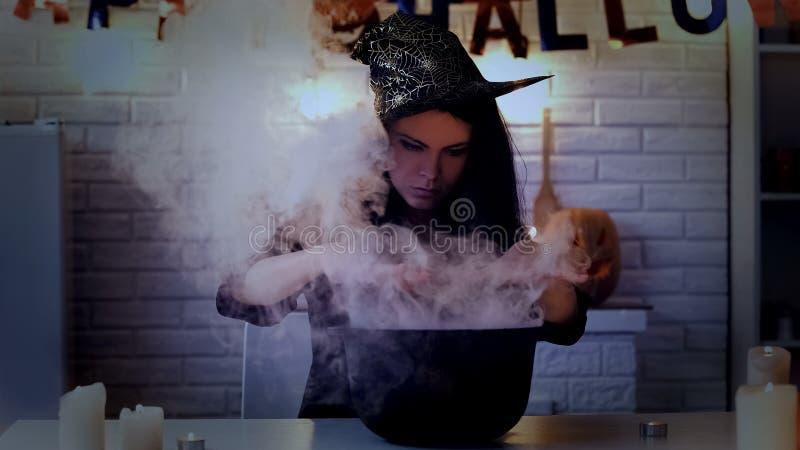 Geheimzinnige jonge vrouw in het kokende drankje van het heksenkostuum, die voor Halloween voorbereidingen treffen stock afbeelding