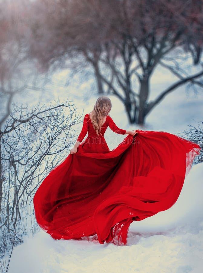 Geheimzinnige meisjeslooppas, die in een rode kleding, met een zeer lange trein spinnen Het haar vliegt in de wind Foto zonder ee royalty-vrije stock fotografie