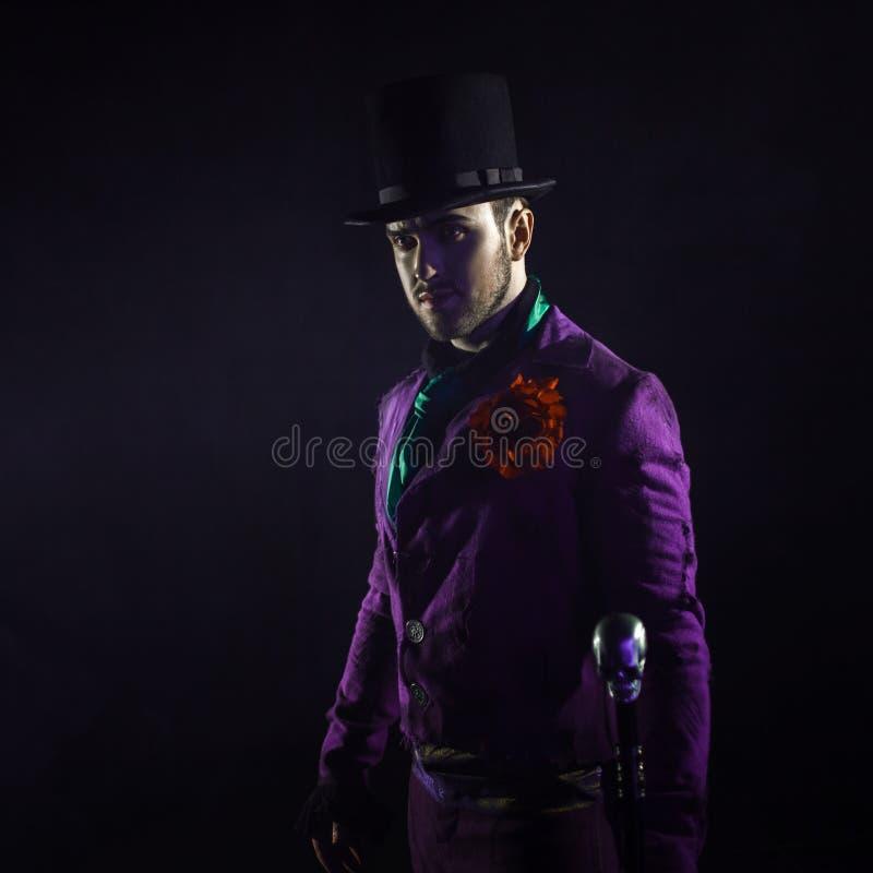 Geheimzinnige mens in een kostuum, met een riet, in een cilinder Donkere achtergrond Eng en sinister Joker, Halloween-kostuum stock afbeeldingen