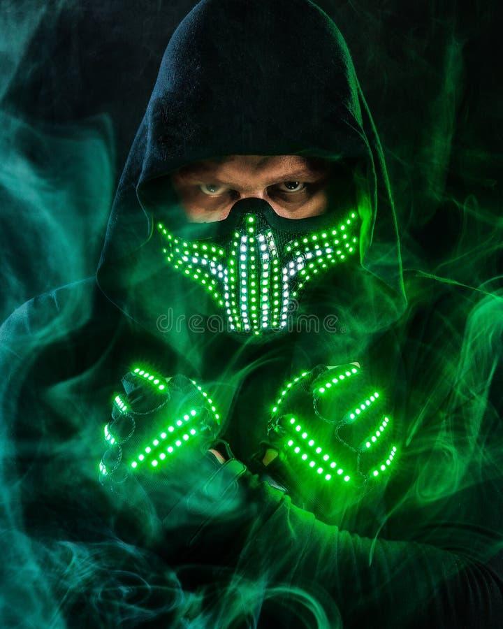 Geheimzinnige mens in zwarte slijtage, neonmasker en handschoenen Karakterpredikant of tovenaar in robe van de toekomst Moordenaa royalty-vrije stock foto