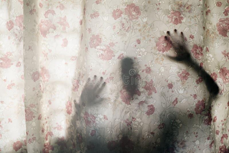 Geheimzinnige menselijke schaduw achter een gordijn stock fotografie