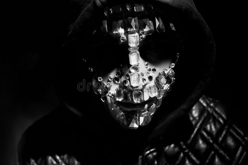 Geheimzinnige mystieke verschijning van een mens Kunstportret van een mens met een kap met grote bergkristallen op zijn gezicht D stock foto