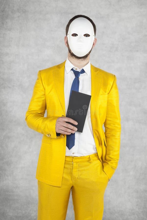 Geheimzinnige politicus die een masker dragen, die een envelop met a houden royalty-vrije stock afbeelding