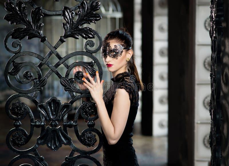 Geheimzinnige vrouw in Venetiaans Carnaval-masker dichtbij smeedijzerpoort stock foto