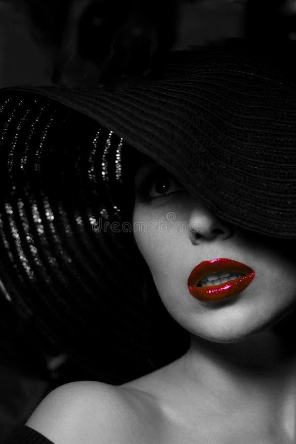 Geheimzinnige vrouw in zwarte hoed. Rode lippen royalty-vrije stock afbeelding
