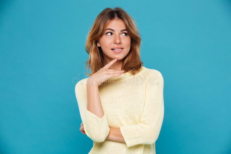 Geheimzinnigheid bijt de speelse vrouw in sweater haar lip stock foto's