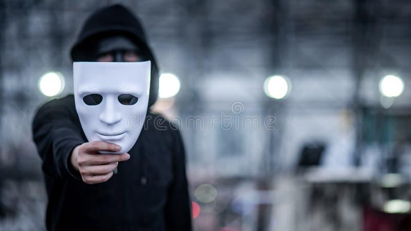 Geheimzinnigheid hoodie mens met zwart masker die wit masker in zijn hand houden Het anonieme sociale maskeren of bipolair wanord stock fotografie