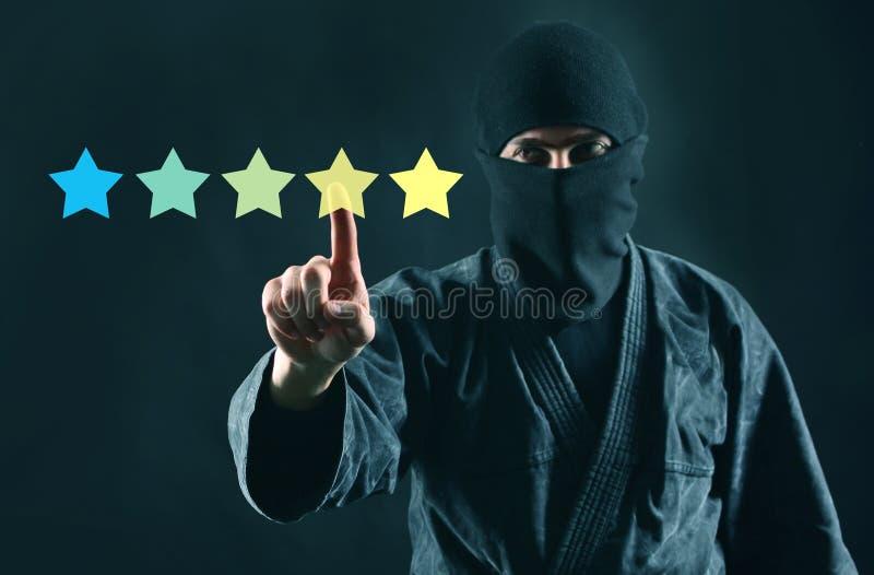 Geheimzinnigheid klant of overzichts online concept Online het schatten 5 sterrenoverzicht en ninja in masker op een donkere acht royalty-vrije stock afbeeldingen