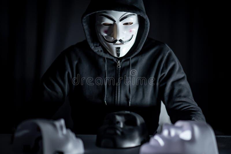 Geheimzinnigheid mens die masker op de lijst kiezen stock afbeelding