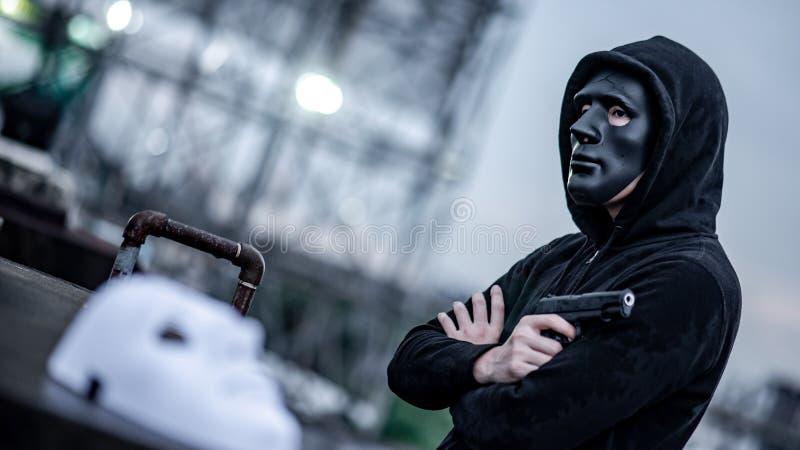 Geheimzinnigheid mens in het zwarte kanon van de maskerholding stock foto's