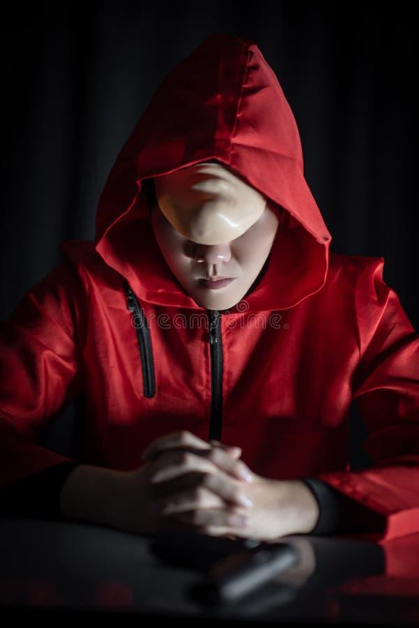 Geheimzinnigheid mens in rode hoodiezitting in dark royalty-vrije stock afbeeldingen