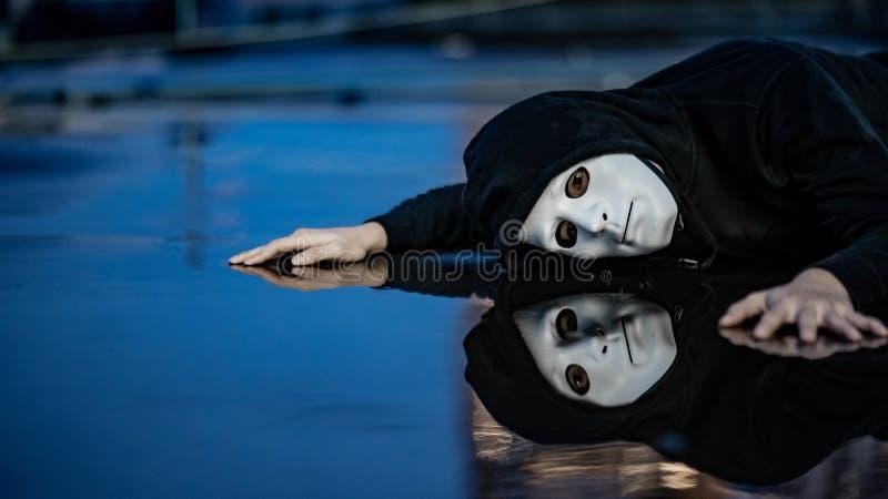 Geheimzinnigheid mens in wit masker die op natte vloer liggen royalty-vrije stock afbeeldingen