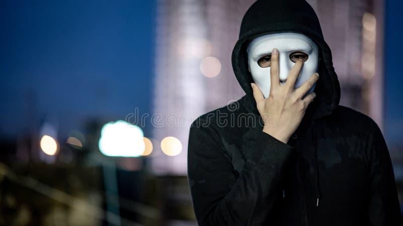 Geheimzinnigheid mens in wit masker die zich op dak bevinden royalty-vrije stock foto's