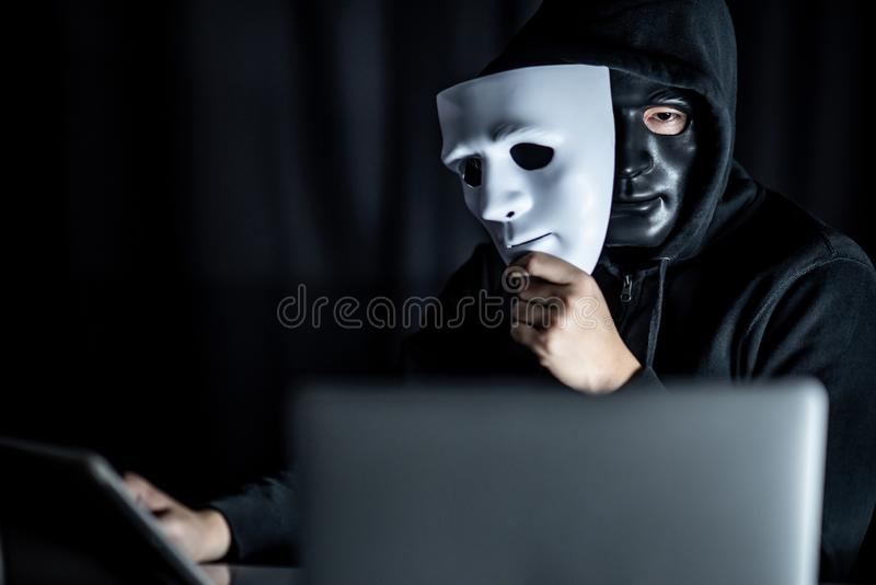 Geheimzinnigheid mens in zwart masker die wit masker houden stock foto