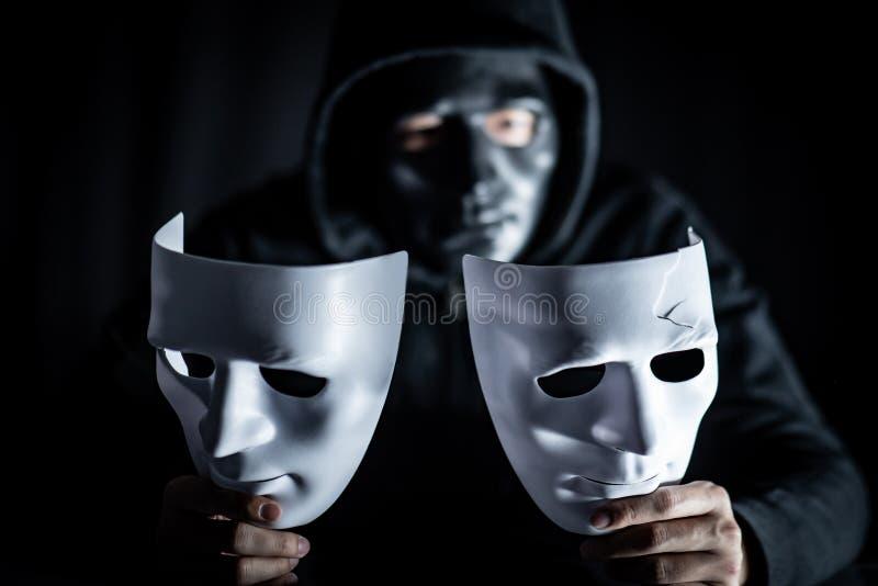 Geheimzinnigheid mens in zwart masker die witte maskers houden royalty-vrije stock foto's