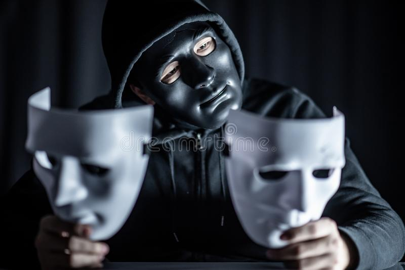 Geheimzinnigheid mens in zwart masker die witte maskers houden royalty-vrije stock afbeelding