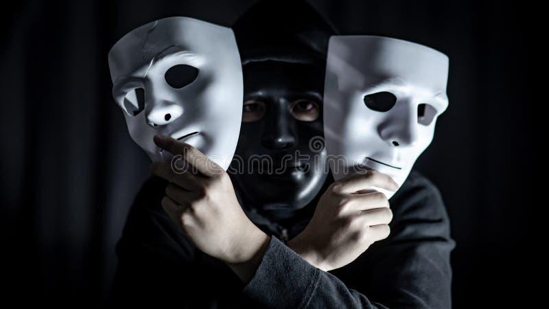Geheimzinnigheid mens in zwart masker die witte maskers houden royalty-vrije stock afbeeldingen