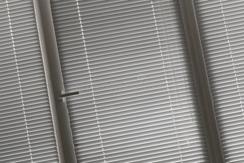 Gehelde mening over grijze horizontale jaloezie in venster stock afbeelding
