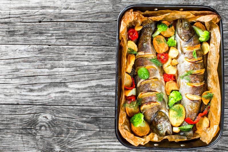 Gehele die forelvissen met aardappels, broccoli, citroen worden geroosterd stock foto