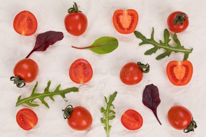 Gehele en gehalveerde tomaten op bloem, arugula en basilicum stock fotografie