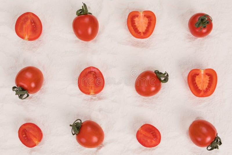 Gehele en gehalveerde verse tomaten op bloem stock afbeeldingen