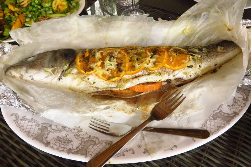 Gehele gebakken zeebaars die met sinaasappel, lavendel en venkel wordt gevuld stock foto