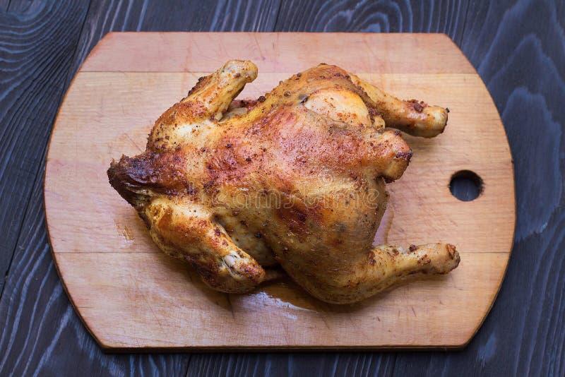 Gehele gebraden kip in kruiden op een houten dienblad stock fotografie