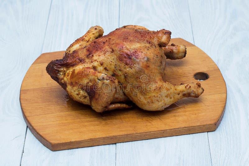 Gehele gebraden kip in kruiden op een houten dienblad stock afbeelding