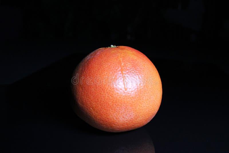Gehele grapefruit op zwarte weerspiegelende studioachtergrond Geïsoleerde zwarte glanzende spiegel weerspiegelde achtergrond voor stock afbeeldingen