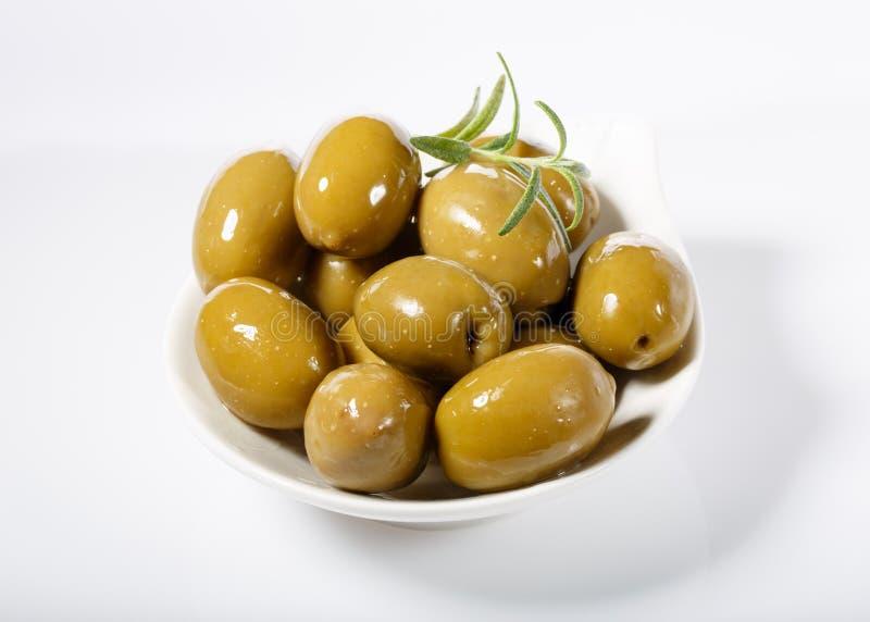 Gehele groene olijven in witte kom stock afbeelding