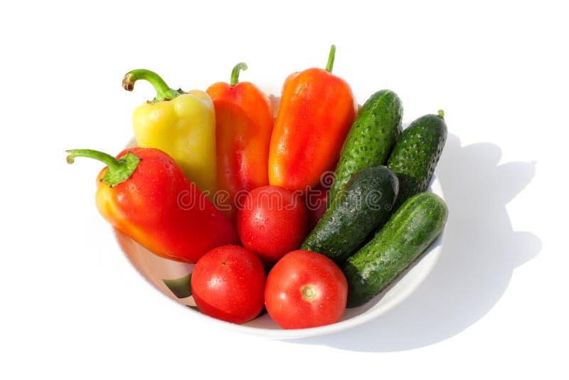 Gehele Groentenkomkommers, Groene paprika's en Tomaten rode groene geeloranje in waterdalingen op witte achtergrond Geïsoleerde h stock afbeeldingen