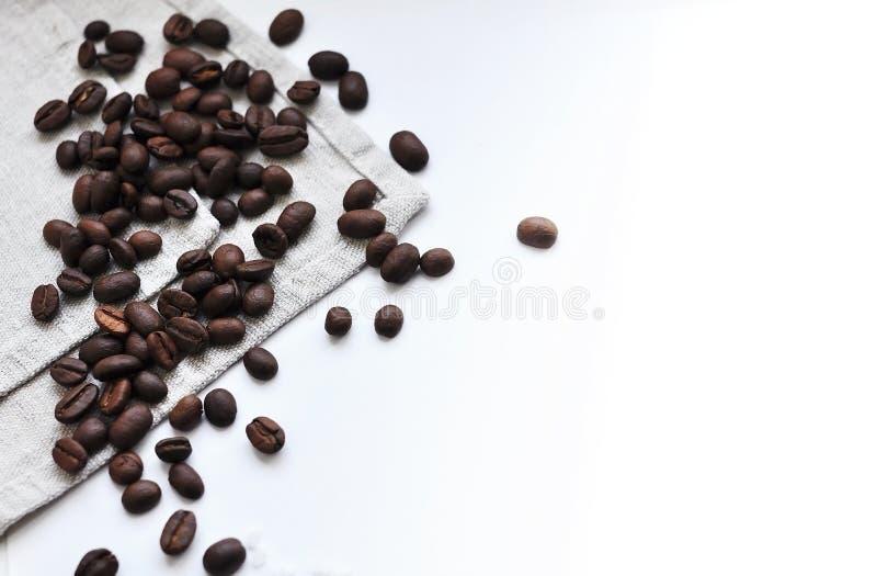 Gehele korrels van geroosterde zwarte die koffie op een linnenhanddoek wordt verspreid stock foto