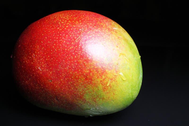 Gehele mango op zwarte weerspiegelende studioachtergrond Geïsoleerde zwarte glanzende spiegel weerspiegelde achtergrond voor elk  stock fotografie