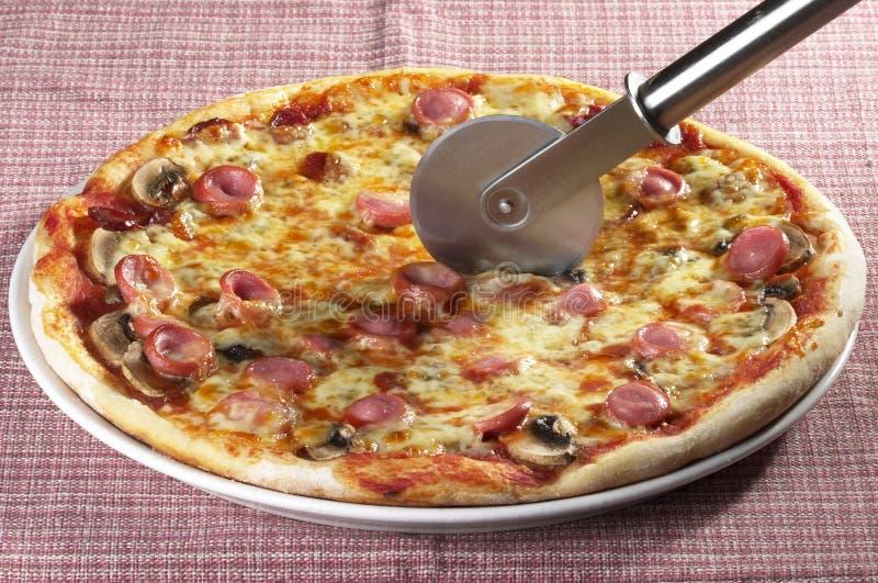 Gehele pizza met een mes stock fotografie